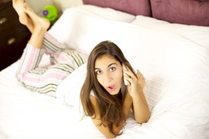 surprised woman talking on the phone in bed at home